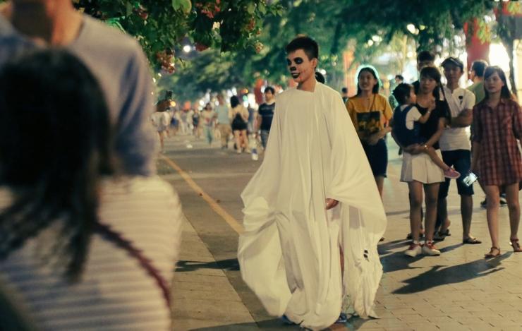 Một nam thanh niên giả ma bằng cách mặc nguyên bộ đồ màu trắng